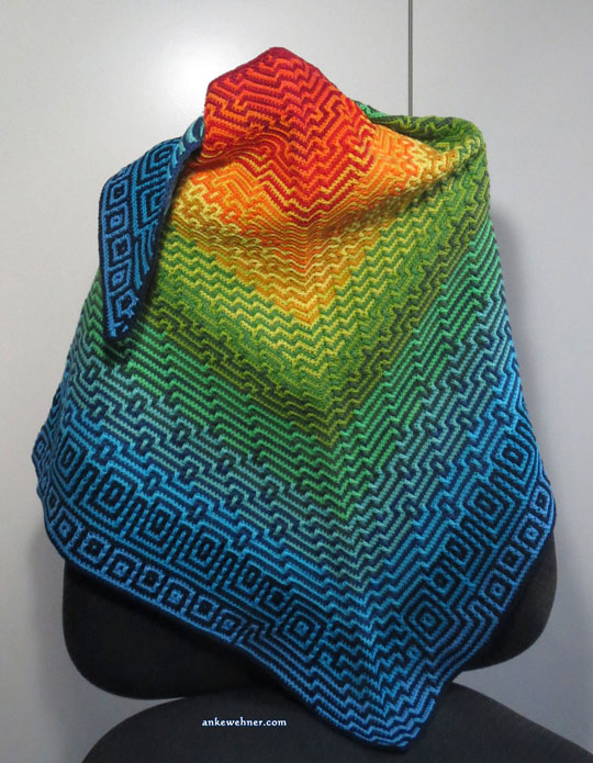A triengular, crocheted shawl, with geometric patterns in a gradient from red in the centre to blue at the edges, draped over the back of an office chair.