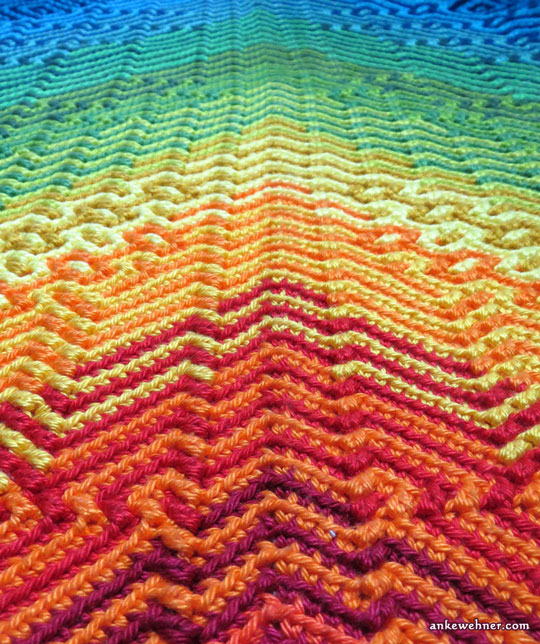 Closeup image, taken at an angle, of a crocheted shawl with geometric patterns, red and irange near the camera, going through yellow and green to blue.
