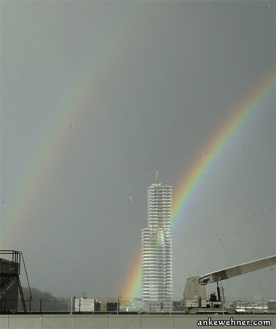 A bringht rainbow crossing an office tower, with a paler rainbow parallelling it, on a background of grey cloud cover (photo)